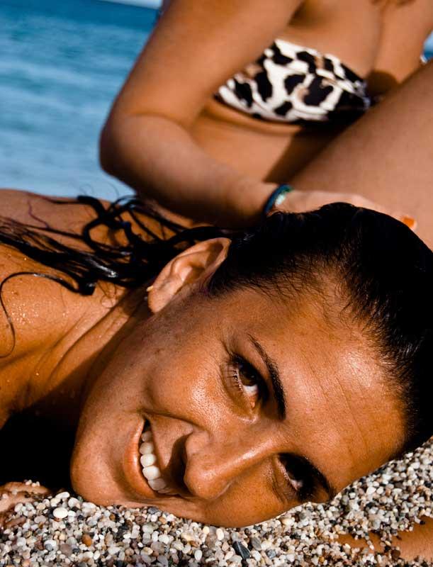 Primer plano de cara. Joven tumbada sobre la arena.